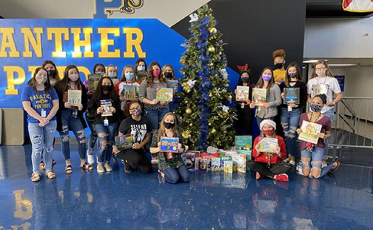 Interact Club members at Palatka High School with books they gathered for students at James A. Long Elementary School. The donation helped the school provide each of its students with a book and a blanket for the holidays.