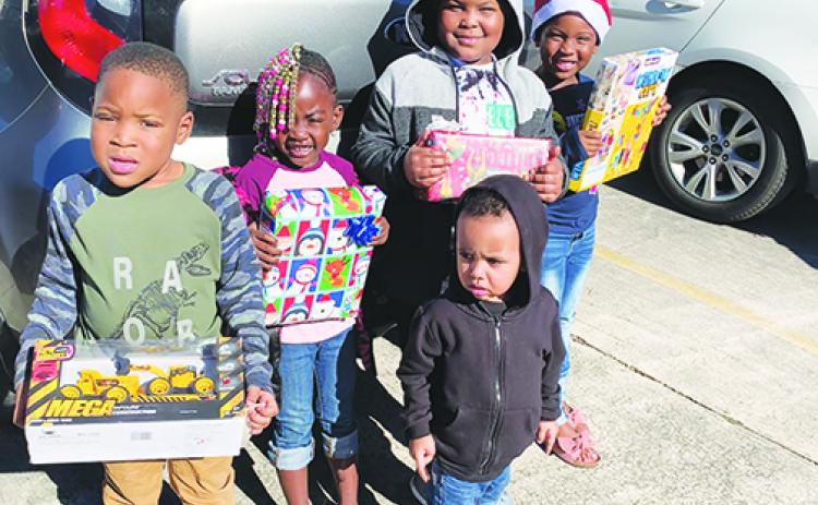 Jahvire Honor, Derrikay McDuffie, Kayden Nelson, Raheme Betts Jr. and Jahzaiya Honor hold toys they received from the Palatka Housing Authority's toy giveaway.