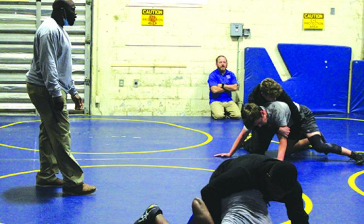 Assistant coach Elijah Campbell (left) and head coach Josh White (in back) watch Palatka High wrestlers go through wrestling battles in practice on Tuesday. (MARK BLUMENTHAL / Palatka Daily News)